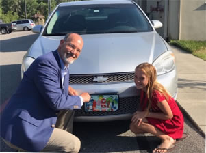 man and girl with custom license plate